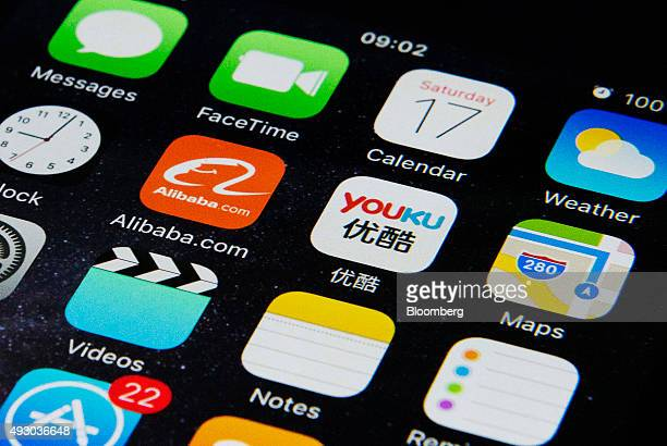 The Alibaba Group Holding Ltd app icon center left and the Youku Tudou Inc app icon center right sit displayed on an Apple Inc iPhone smart device...