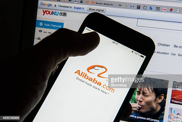 The Alibaba Group Holding Ltd app logo is displayed on an Apple Inc iPhone 6 smartphone screen is held in front of the Youku Tudou Inc website in...