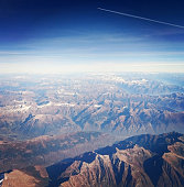 Aerial view of the austrian alps with deep blue sky and another airplane flying over in the distance