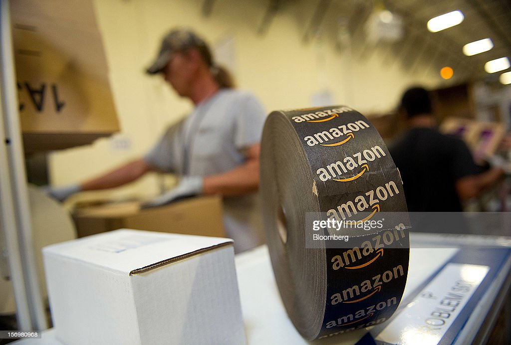 The Amazon.com Inc. logo is seen on a roll of tape arranged for a photograph at the company's distribution center in Phoenix, Arizona, U.S. on Monday, Nov. 26, 2012. U.S. retailers are extending deals into Cyber Monday and beyond to try to sustain a 13 percent gain in Thanksgiving weekend sales. Photographer: David Paul Morris/Bloomberg via Getty Images