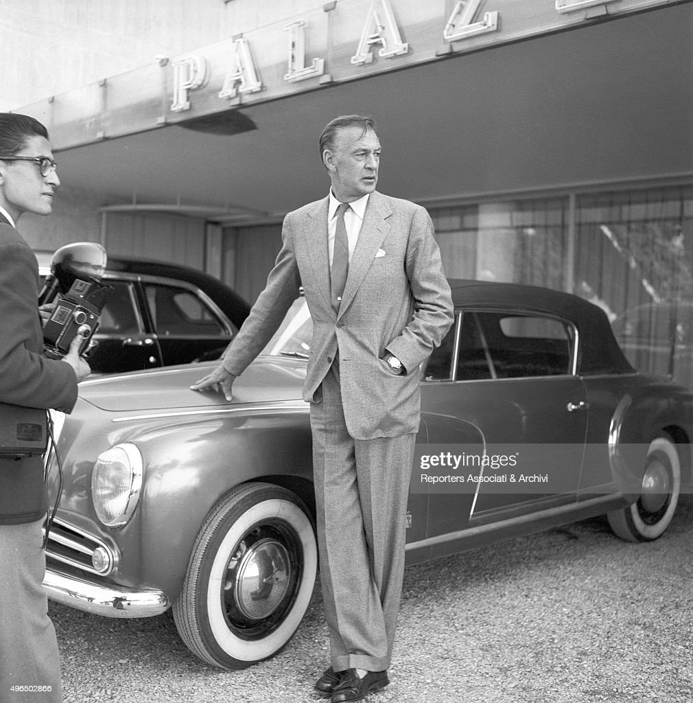The American actor Gary Cooper posing beside a car Rome 1957