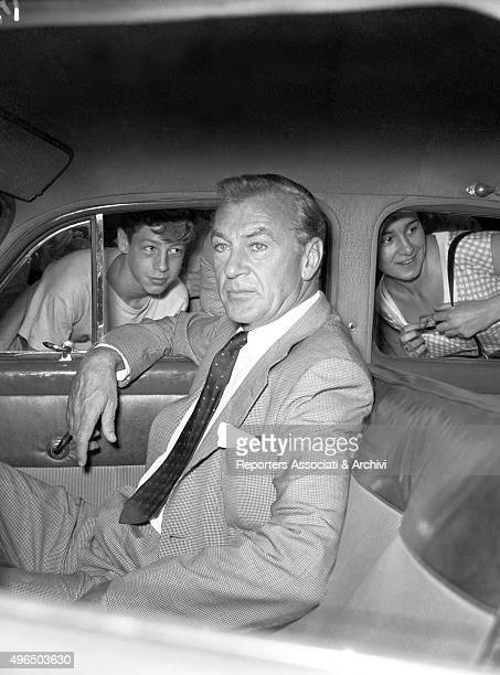 The American actor Gary Cooper sitting on a car Two intrigued boys are looking at him through the windows Rome 1957