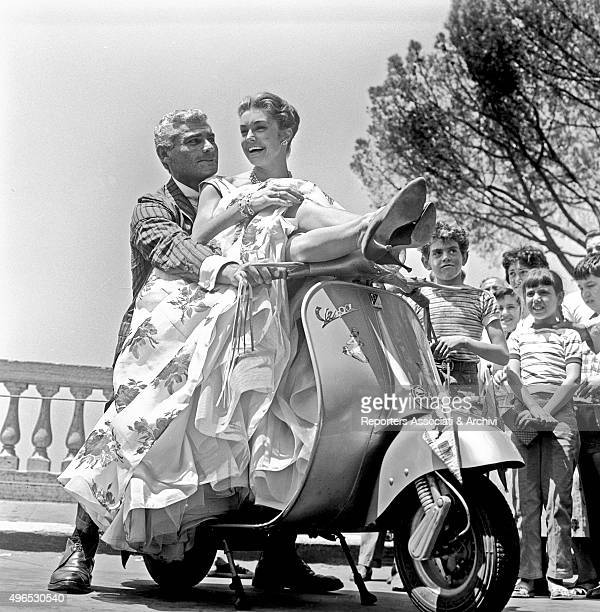 The American actor Jeff Chandler posing on a Vespa with American actress and swimmer Esther Williams on the terrace of the Pincio in Rome Rome 1958