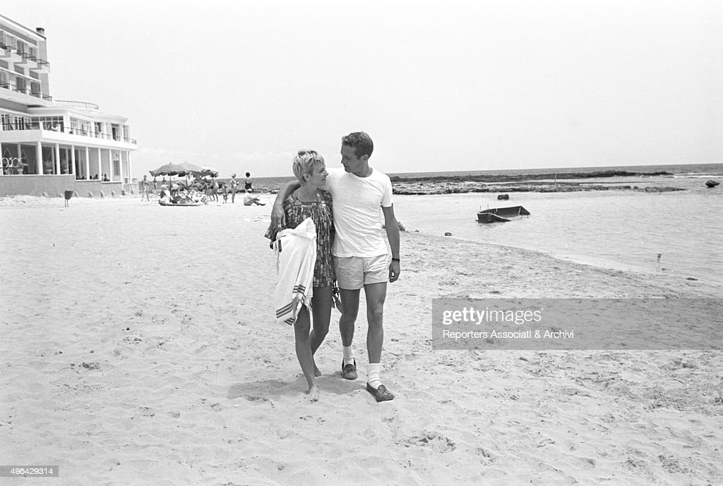 The American actor Paul Newman walking on a beach hugging the American actress producer and wife Joanne Woodward during a break in the shooting of...