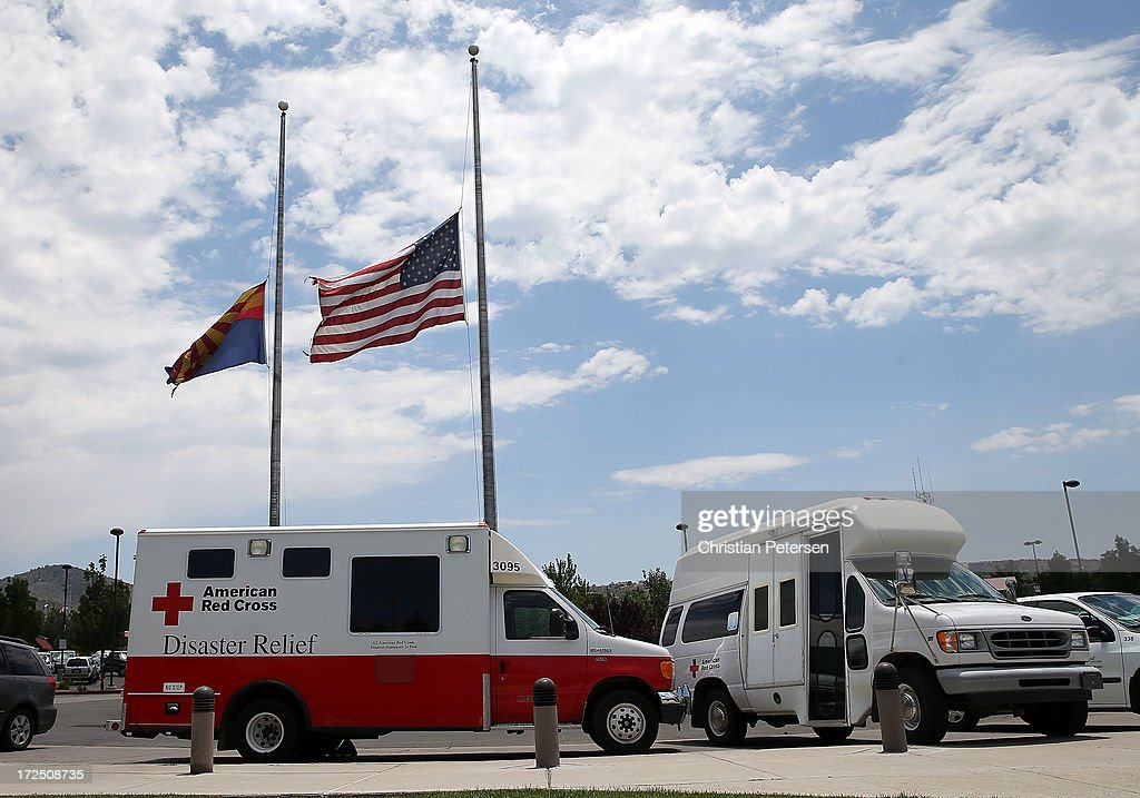 The American and State of Arizona flags fly at half mast outside of Yavapai College for victims of the Yarnell Hill wildfires on July 2, 2013 in Prescott, Arizona. The Red Cross is providing families displaced by the fires in Yarnell, AZ food and shelter. Nineteen Granite Mountain Interagency Hotshot Crew firefighters died battling the fast-moving wildfire that has burned nearly 8, 400 acres.