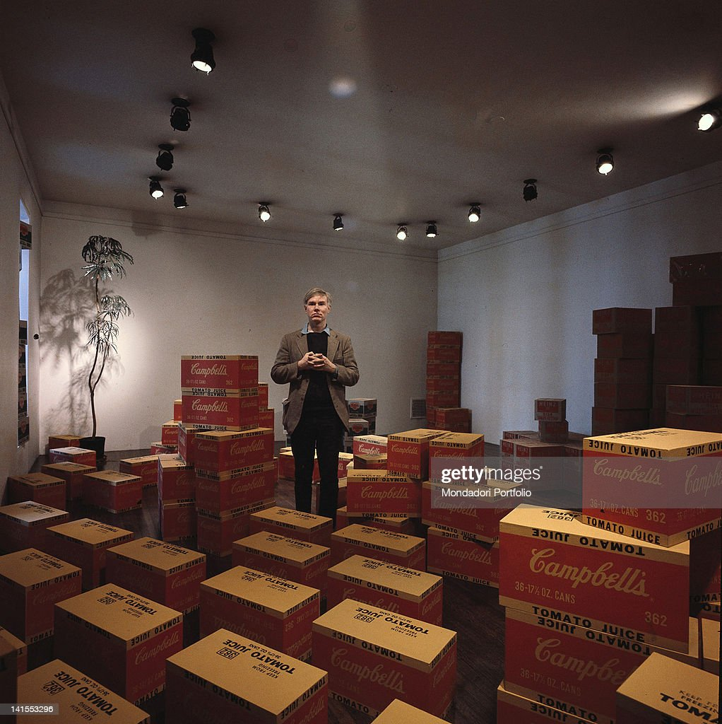 The American artist <a gi-track='captionPersonalityLinkClicked' href=/galleries/search?phrase=Andy+Warhol&family=editorial&specificpeople=123830 ng-click='$event.stopPropagation()'>Andy Warhol</a> posing inside his studio among cases of Campbell tomato juice. New York, 1964