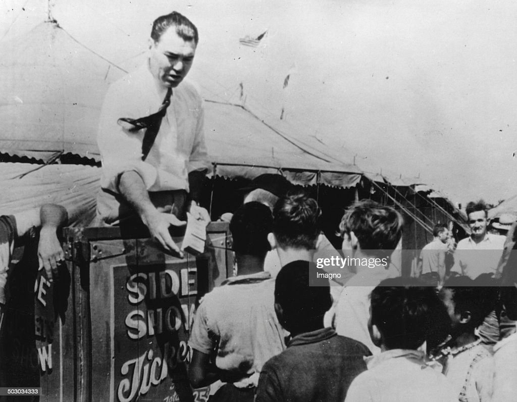 The American boxer <a gi-track='captionPersonalityLinkClicked' href=/galleries/search?phrase=Jack+Dempsey+-+Boxer&family=editorial&specificpeople=15348667 ng-click='$event.stopPropagation()'>Jack Dempsey</a> sells tickets in front of a circus in Portsmouth / Virginia. In the circus he works as a referee in boxing matches. 13th August 1941. Photograph.