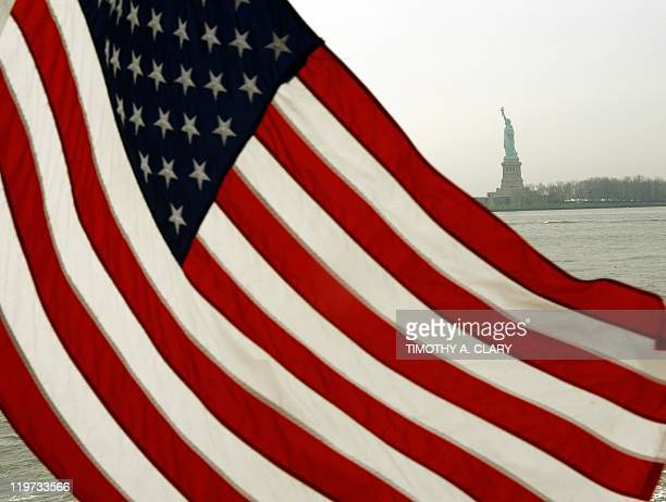 The American Flag blows in the wind off the back of the Ellis Island/Liberty Island Ferry with the Statue of Liberty in the background following the...