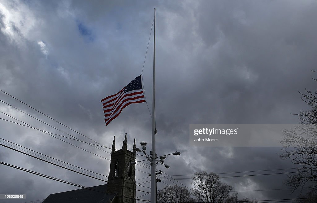The American flag flies at half-staff on December 21, 2012 in Newtown, Connecticut. Church bells rang out at 9:30 EST to mark the one-week anniversary of the Sandy Hook Elementary School massacre.
