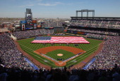 The American Flag is displayed on the field as the national anthem is observed prior to the game between the San Francisco Giants and the Colorado...