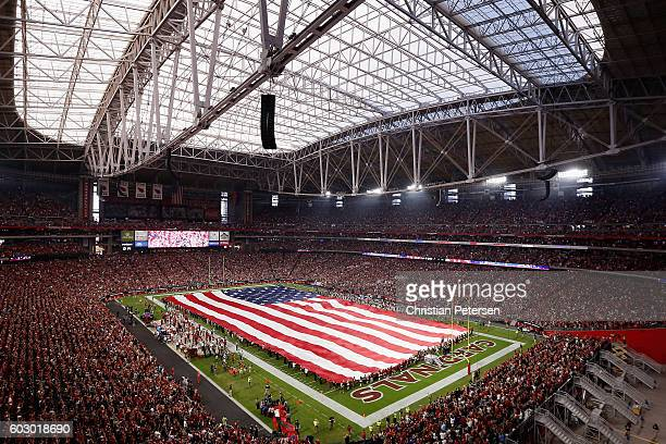 The american flag is draped across the field for the national anthem to the NFL game between the Arizona Cardinals and the New England Patriots at...