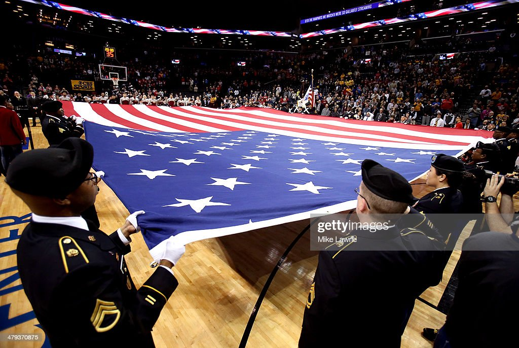 The American Flag is held on the court as the National Anthem is sung before the game between the Virginia Commonwealth Rams and the Saint Joseph's...