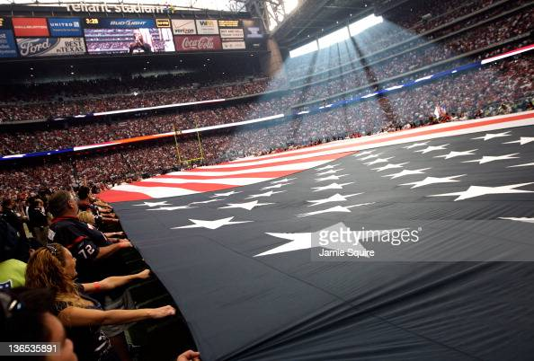 The American flag is held on the field during the national anthem before the Houston Texans take on the Cincinnati Bengals during their 2012 AFC Wild...