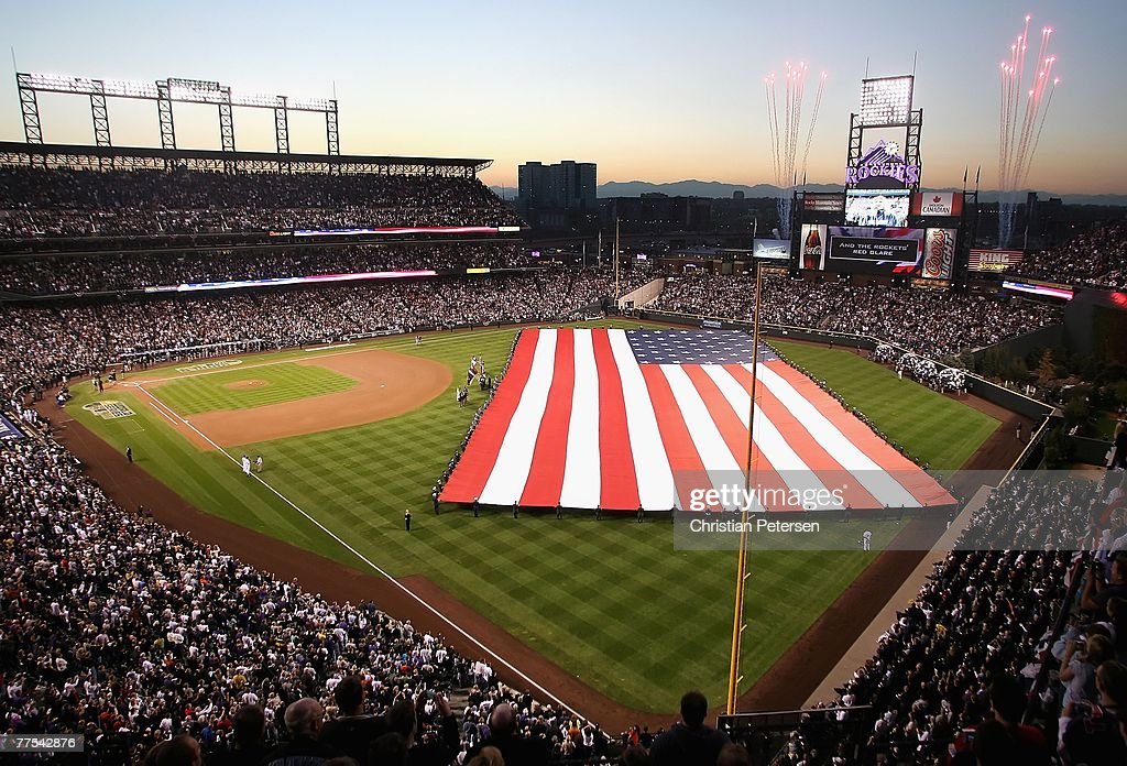 The American Flag is stretched across the outfield as the National Anthem is performed by Trisha Yearwood before Game Four of the 2007 World Series...