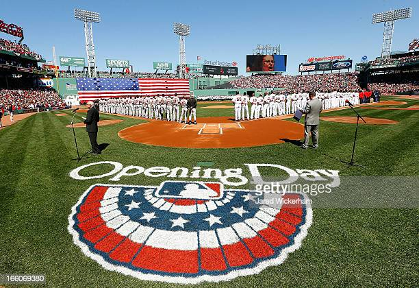 The American flag is unfurled over the Green Monster while the national anthem is sung prior to the Opening Day game between the Boston Red Sox and...