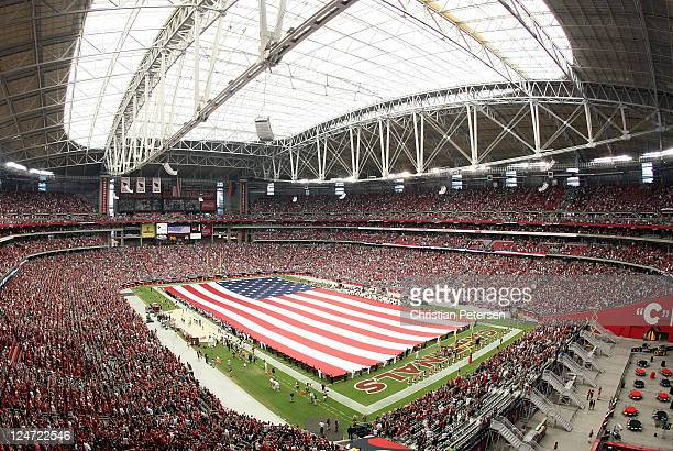 The American flag is unveiled on the field as Jordin Sparks performs the National Anthem before the NFL season opening game between the Carolina...