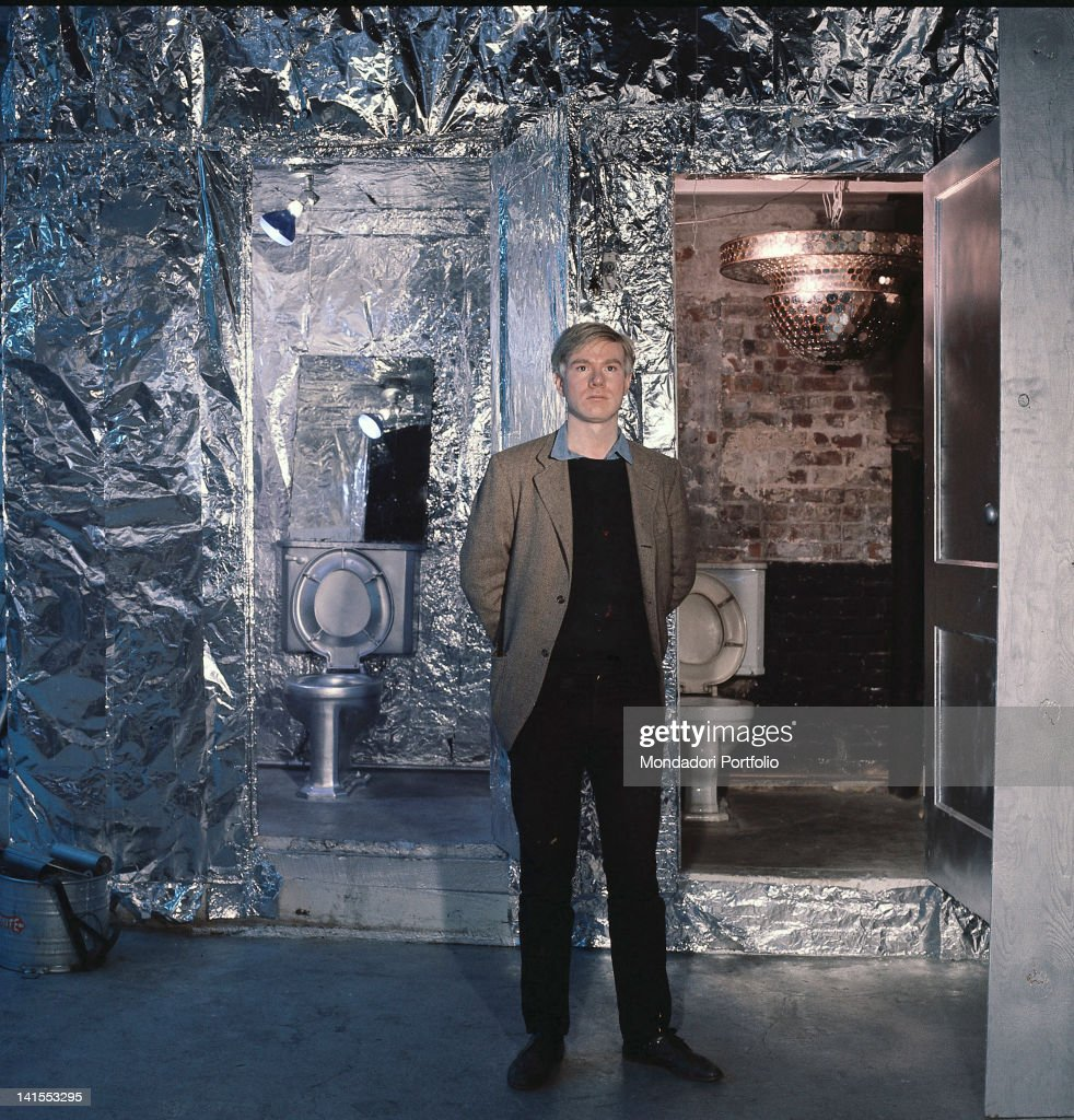 The American painter and director <a gi-track='captionPersonalityLinkClicked' href=/galleries/search?phrase=Andy+Warhol&family=editorial&specificpeople=123830 ng-click='$event.stopPropagation()'>Andy Warhol</a> posing in his studio in front of two toilets. New York, 1964
