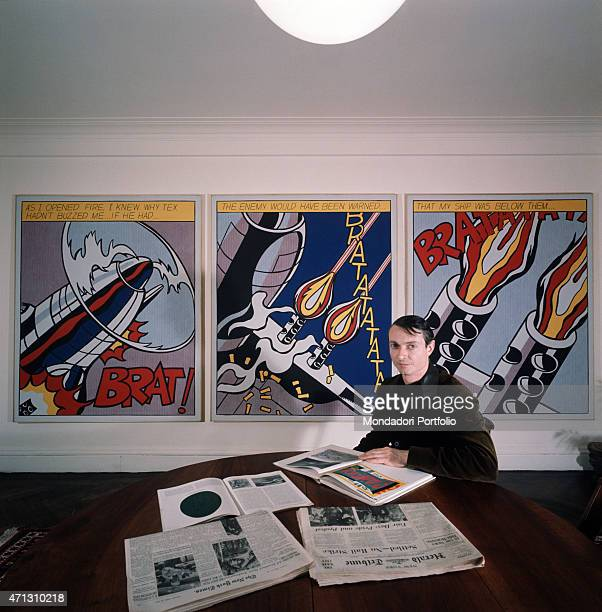 The American painter and exponent of Pop Art Roy Lichtenstein is sitting at a table and is attentively looking through some magazines over his...