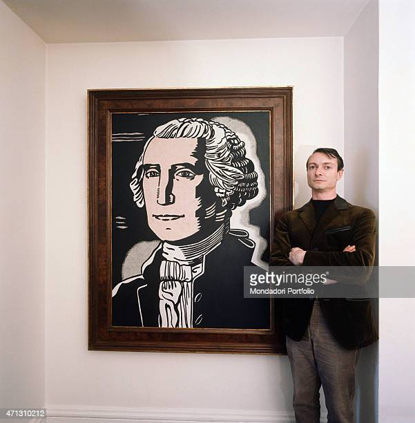 The American painter and representatvie of Pop Art Roy Lichtenstein poses seriously with his arms folded and close to one of his pictures 1964