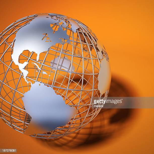 The Americas being shown on metal globe against orange
