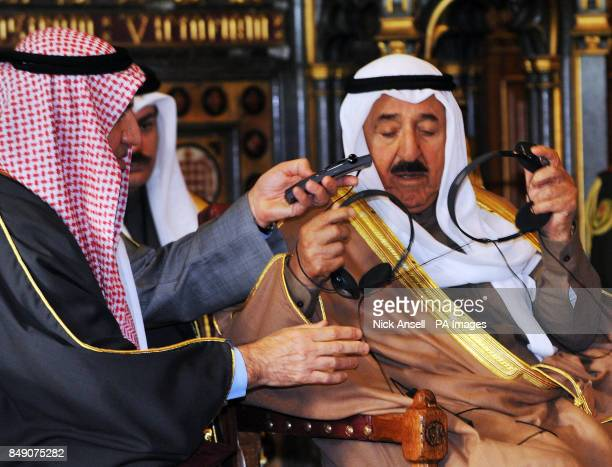 The Amir of the State of Kuwait His Highness Sheikh Sabah AlAhmad AlJaber AlSabah gets tangled in wires as an aide passes him a new headset in the...