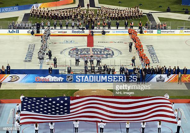 The Anaheim Ducks and the Los Angeles Kings stand during the national anthem as part of the 2014 Coors Light NHL Stadium Series on January 25 2014 in...