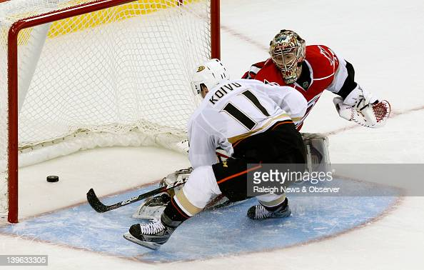 The Anaheim Ducks' Saku Koivu puts the puck past Carolina Hurricanes goalie Justin Peters for the winning goal in the shootout at the RBC Center in...