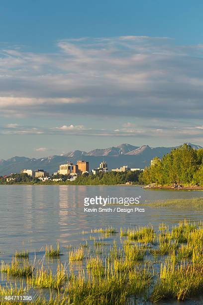 The anchorage city skyline seen from the tony knowles coastal trail during high tide chugach mountains in the background