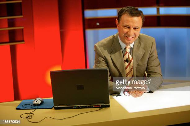 The anchorman Antonello Piroso is smiling while seated at a desk with joined hands during the special Tg Lasette In the closeup a portable computer...