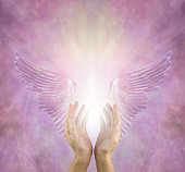 female healer with hands reaching up between silver lilac angel wings and a bright white light against a pink lilac energy background with copy space above
