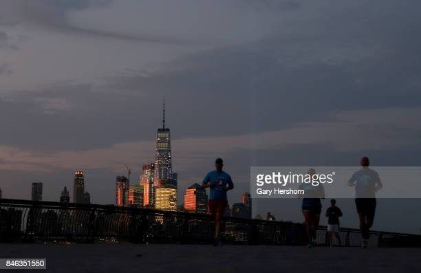 The annual Tribute in Light begin to fade over lower Manhattan as the sun rises in New York City on September 12 2017 as seen from Hoboken New Jersey