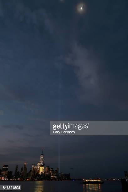 The annual Tribute in Light passes by the moon as the begin to fade over lower Manhattan as the sun rises in New York City on September 12 2017 as...