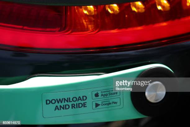 The Apple Inc and Google Inc Play app store logos sit on a Coup eScooter electric hire vehicle operated by Robert Bosch GmbH in Berlin Germany on...