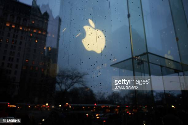 The Apple logo is seen reflected on the glass of its store on Fifth Avenue in New York on February 23 2016 Apple is battling the US government over...