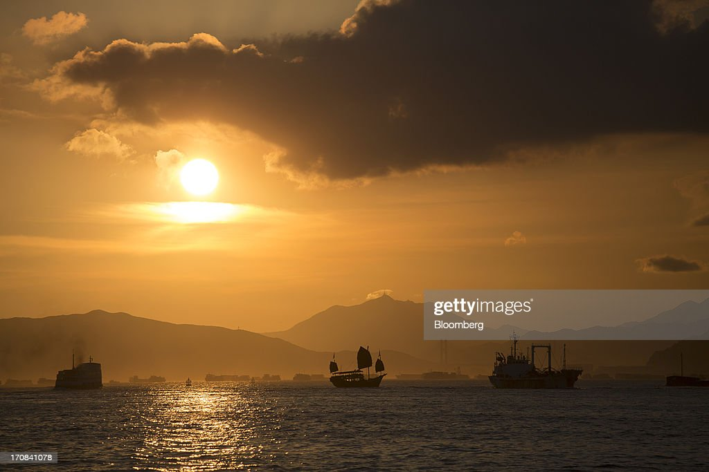The Aqua Luna junk, a tour boat operated by Aqua Restaurant Group, center, sails in Victoria Harbor as the sun sets in Hong Kong, China, on Tuesday, June 18, 2013. A shortage of housing, low mortgage costs and a buying spree by mainland Chinese have led home prices to more than double since the beginning of 2009, shrugging off repeated attempts by the government to curb gains amid an outcry over affordability. Photographer: Jerome Favre/Bloomberg via Getty Images