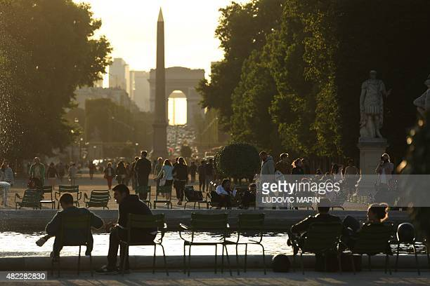 The Arc de Triomphe and the Luxor Obelisk are seen in the distance as people sit near a fountain at the Tuileries Garden in central Paris at sunset...