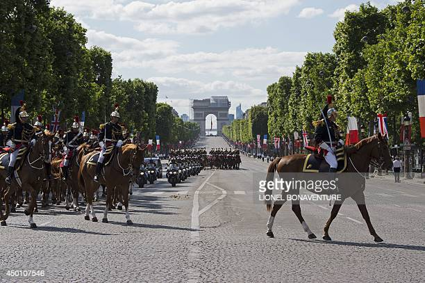 The Arc de Triomphe is seen in the background as the motorcade of Britain's Queen Elizabeth II and French President Francois Hollande drives down the...