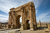Algeria. Timgad (ancient Thamugadi or Thamugas). Triumphal arch, called Trajan's Arch (Corinthian order with three arches) and fragment of Decumanus Maximus street. Please see my other images of the R