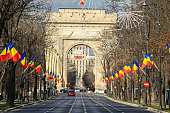 The Arch of Triumph (Arcul de Triumf) from Bucharest Romania, National Day with romanian flags, view from Kisseleff Avenue.