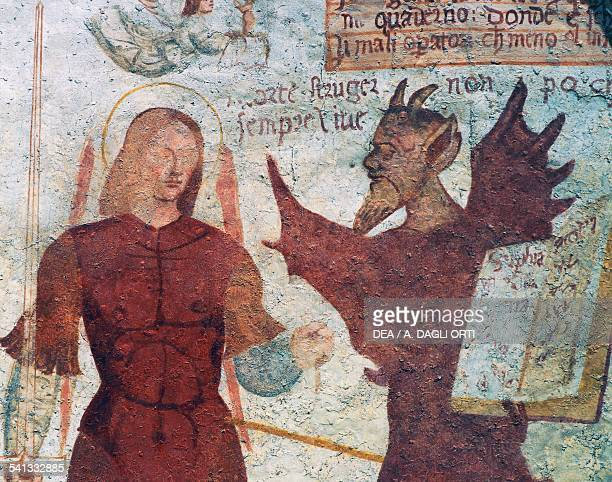 The Archangel Michael and the devil with the book of the seven deadly sins detail from The Dance of Death fresco by Simone II Baschenis San Vigilio...