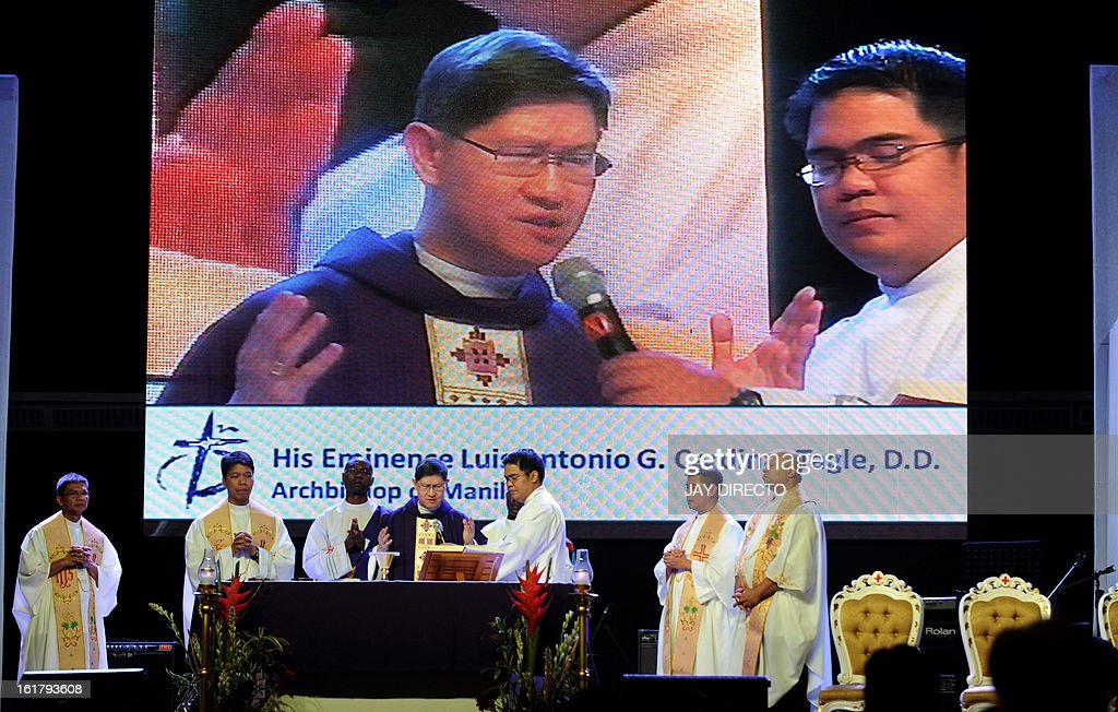 The Archbishop of Manila Cardinal Luis Antonio Tagle's image appears on a screen as he stands below (4th L) giving mass to the faithful at a Catholic gathering in Manila on February 16, 2013. Filipinos are hoping that 55-year-old Tagle, who was only made a cardinal last year, could become the next pope following the shock announcement by 85-year-old Pope Benedict XVI that he would resign because of health reasons. AFP PHOTO / Jay DIRECTO