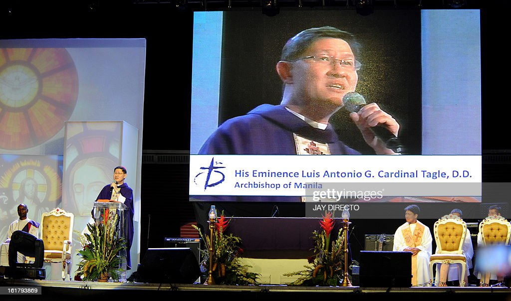 The Archbishop of Manila Cardinal Luis Antonio Tagle's image appears on a screen as he stands below (2nd L) giving mass to the faithful at a Catholic gathering in Manila on February 16, 2013. Filipinos are hoping that 55-year-old Tagle, who was only made a cardinal last year, could become the next pope following the shock announcement by 85-year-old Pope Benedict XVI that he would resign because of health reasons. AFP PHOTO / Jay DIRECTO