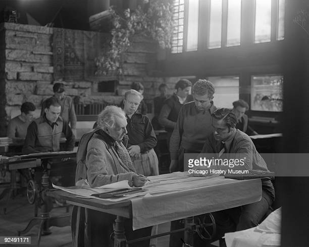 The architect Frank Lloyd Wright at a drafting table with three onlookers while at Taliesin East in Spring Green WI December 1937