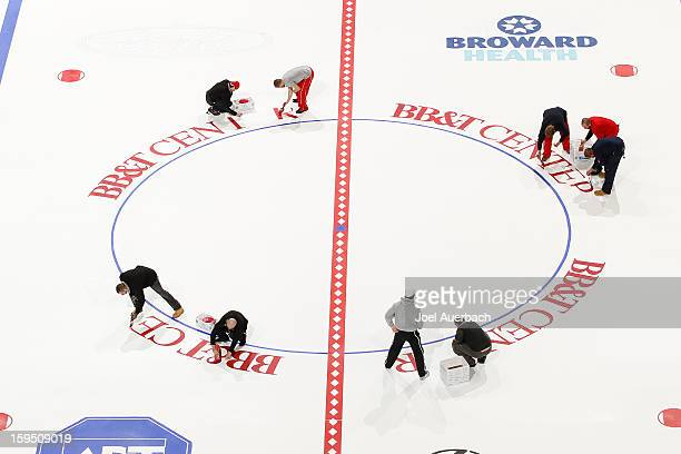 The arena's new name is painted around the center ice face off circle by members of the Florida Panthers crew at the BBT Center on January 14 2013 in...