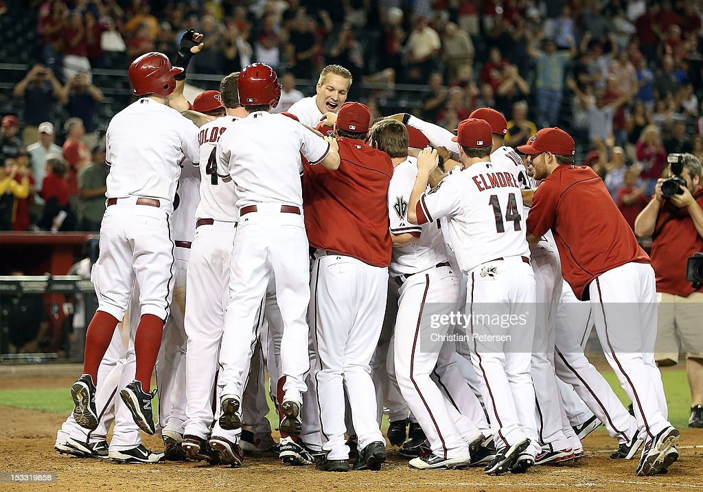The Arizona Diamondbacks celebrate around Aaron Hill #2 after he hit a walk off three run home run against the Colorado Rockies during the ninth inning of the MLB game at Chase Field on October 2, 2012 in Phoenix, Arizona. The Diamondbacks defeated the Rockies 5-3.