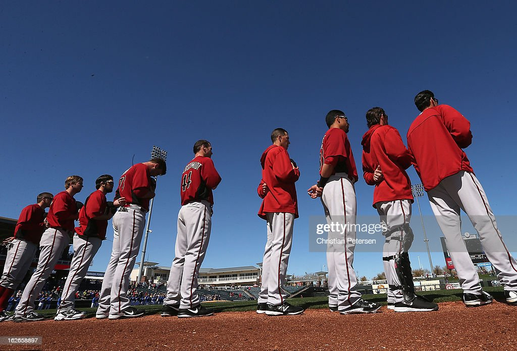 The Arizona Diamondbacks stand atteneded for the National Anthem before the spring training game against the Kansas City Royals at Surprise Stadium on February 25, 2013 in Surprise, Arizona.