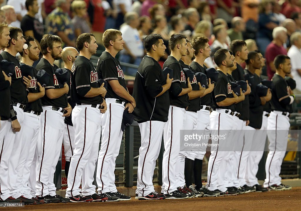 The Arizona Diamondbacks stand in silence to honor the 19 Granite Mountain Interagency Hotshot Crew firefighters who died battling a fast-moving wildfire near Yarnell, AZ before the MLB game between the Arizona Diamondbacks and the Colorado Rockies at Chase Field on July 5, 2013 in Phoenix, Arizona.