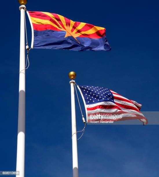 The Arizona state flag flies beside the United States flag at the Visitor Center at Canyon de Chelly National Monument near Chinle Arizona...