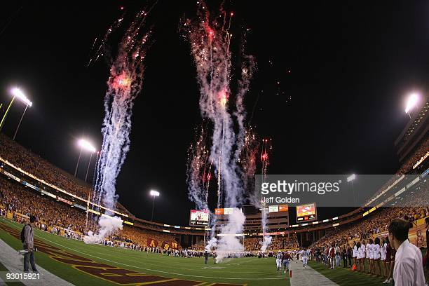 The Arizona State Sun Devils run out onto the field as fireworks light the night sky before the college football game against the USC Trojans on...