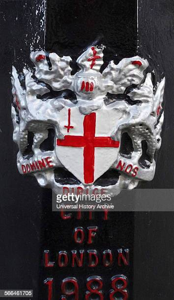 The arms consist of a silver shield bearing a red cross with a red upright sword and a combination of the emblems of the patron saints of England and...